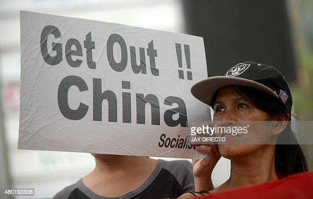 A protester displays a placard during a rally in front of the Chinese Consulate in Manila's financial district on July 10 calling to boycott products...