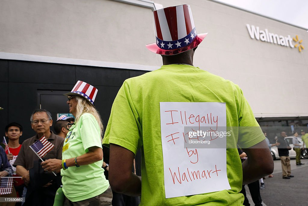 A protester displays a sign saying 'Illegally fired by Walmart' during a demonstration outside a Wal-Mart store in Los Angeles, California, U.S., on Tuesday, July 2, 2013. Southern California community supporters joined Wal-Mart Stores Inc. workers to protest against alleged illegal violations of employees labor rights and freedom of speech. Photographer: Patrick T. Fallon/Bloomberg via Getty Images
