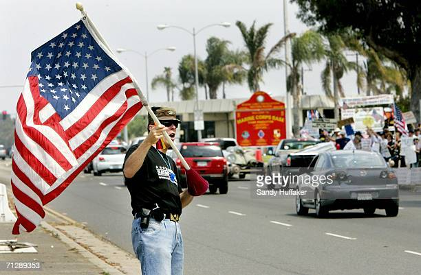 Protester Dr Tom Haggerty waves an American flag in support of the United States military during a protest at the front gate of Camp Pendleton June...