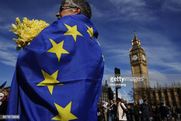 A protester draped in a European Union flag and holding daffodils stands in front of Elizabeth Tower commonly referred to as Big Ben during a Unite...
