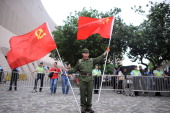 A protester dressed as a Chinese Red Guard holds flags of People's Republic of China and Communist Party of China during a rally on May 1 2014 in...