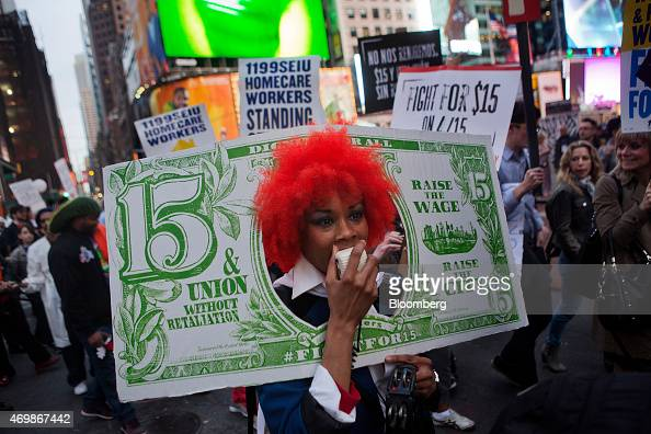 A protester dressed as a fake banknote speaks into a megaphone at a rally in support of minimum wage increase in New York US on Wednesday April 15...