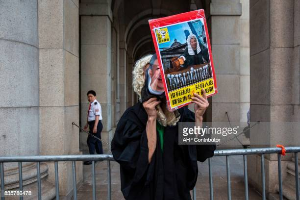 A protester dressed as a judge and with a mask of Chinese President Xi Jinping stands outside the Court of Final appeal after marching in Hong Kong...