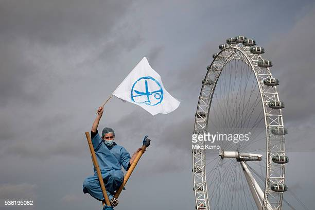 Protester dressed as a nurse waves a flag signifying the cuts to services atop a bamboo tripod with the London Eye behind UK Uncut shut down...