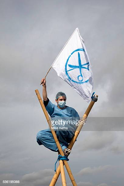 Protester dressed as a nurse waves a flag signifying the cuts to services atop a bamboo tripod UK Uncut shut down Westminster Bridge in a protest...