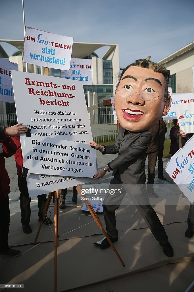 A protester dressed as German Economy Minister Philipp Roesler holds up an altered passage from the government's '4th Poverty And Wealth Report' outside the Chancellery on March 6, 2013 in Berlin, Germany. The government is scheduled to release the report later in the day, following much criticism when it was revealed that Roesler had demanded certain passages be removed or rephrased, including one that refered to the growing inequality of the distribution of wealth in Germany. The number of Germans that fall below the official poverty line has been growing steadily in recent years.
