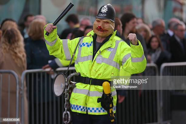 A protester dressed in replica police uniform and pig mask stands close to members of the audience as they wait in line to enter the studios at...