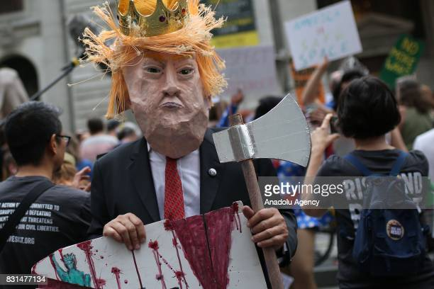A protester dressed up as Donald Trump holds an axe during a rally against US President Donald J Trump for threating North Korea and Venezuela with...
