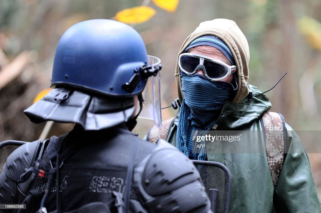 A protester faces French riot police on November 24, 2012 as they seek to evict squatters from protected swampland where Prime Minister Jean-Marc Ayrault wants to build a new airport. Clashes between police and protesters resumed at Notre-Dame-des-Landes, outside the western city of Nantes, as officers fired tear gas and squatters threw stones and glass bottles at them in return. AFP PHOTO / JEAN-SEBASTIEN EVRARD