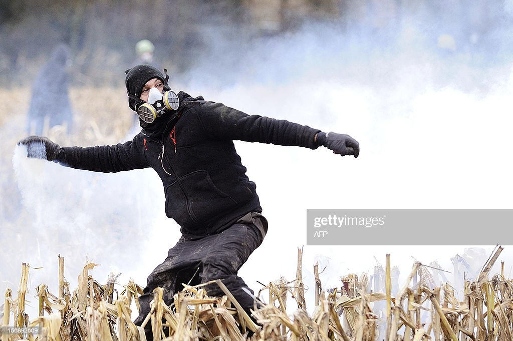 A protester faces on November 24, 2012 French riot police, seeking to evict squatters from protected swampland where Prime Minister Jean-Marc Ayrault wants to build a new airport. Clashes between police and protesters resumed at Notre-Dame-des-Landes, outside the western city of Nantes, as officers fired tear gas and squatters threw stones and glass bottles at them in return.