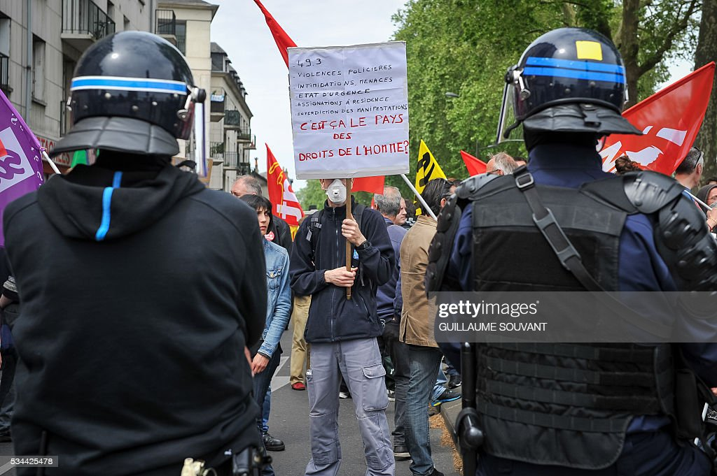 A protester faces riot police during a demonstration against the government's planned labour law reforms on May 26, 2016 in Tours, Central France. The French government's labour market proposals, which are designed to make it easier for companies to hire and fire, have sparked a series of nationwide protests and strikes over the past three months. The sign reads 'It that the country of the human rights ?'. / AFP / GUILLAUME