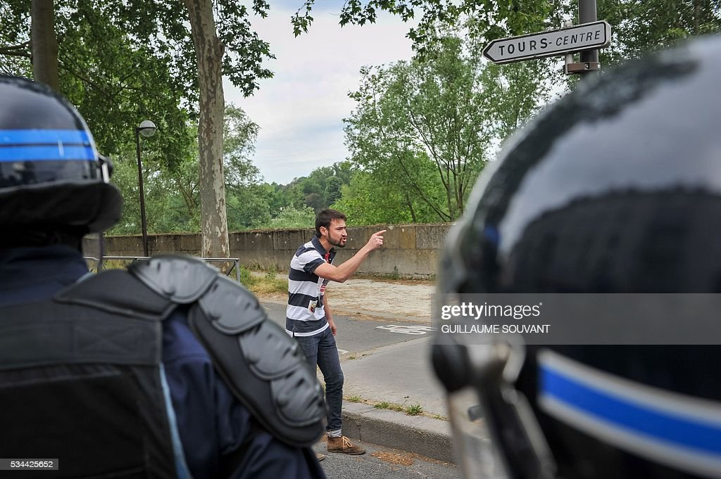 A protester faces riot police during a demonstration against the government's planned labour law reforms on May 26, 2016 in Tours, Central France. The French government's labour market proposals, which are designed to make it easier for companies to hire and fire, have sparked a series of nationwide protests and strikes over the past three months. / AFP / GUILLAUME