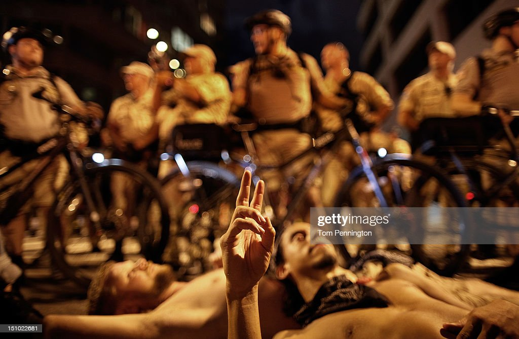 A protester flashes a peace sign while laying in the street during a protest march through downtown as the Republican National Convention wraps up at the Tampa Bay Times Forum on August 30, 2012 in Tampa, Florida. The Republican party delegates affirmed Mitt Romney as the party's nominee for president August 28.