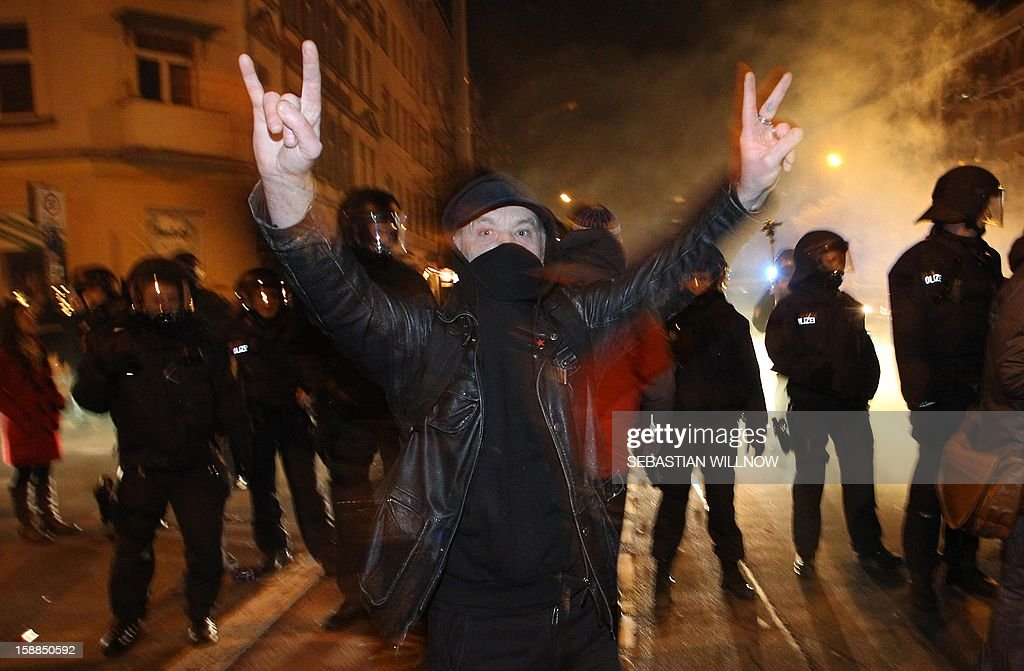 A protester flashes a V-sign in front of policeman during a spontaneous anti-government demonstration on January 1, 2013 in Leipzig, eastern Germany. AFP PHOTO / SEBASTIAN WILLNOW /Germany Out