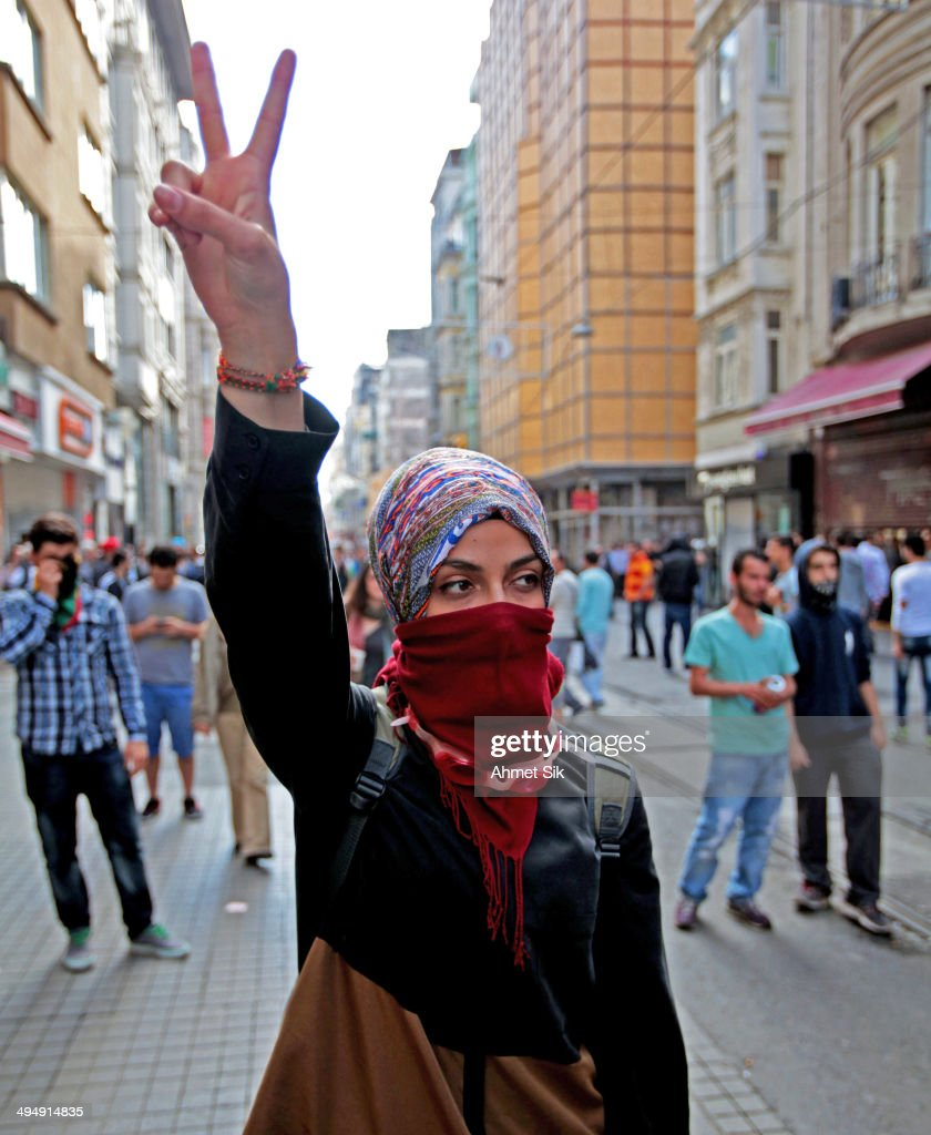 A protester flashes the peace sign during an anti-government protest on May 31, 2014 in Istanbul, Turkey. Turkish police used tear gas in central Istanbul to disperse protesters seeking to mark the one-year anniversary of one the largest anti-government demonstration in decades. Several hundred people gathered on streets leading to Taksim Square, shouting for the government's resignation, when police fired tear gas at the crowd, which quickly scattered.