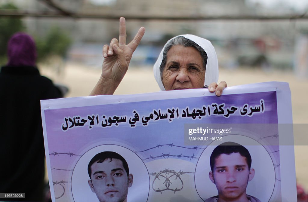 A protester flashes the sign for victory as she holds a poster of Palestinians detained in Israeli jails during a rally to show solidarity with Palestinian prisoners in Gaza city on April 16, 2013. Statistics published by Israeli rights group B'Tselem show by the end of 2012, 4,500 Palestinians were being held in Israeli jails.