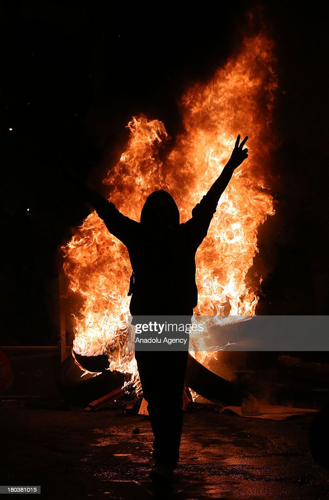 A protester flashes V sign near a fire barricade during a protest over the death of Ahmet Atakan on September 11, 2013 in Dikmen neighborhood of Ankara, Turkey. Ahmet Atakan, a 22-year-old protester in Turkey's southern province of Hatay, died in anti government protests in Hatay.