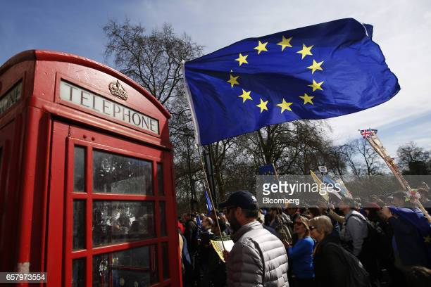 A protester flies a European Union flag past a traditional British red telephone box during a Unite for Europe march to protest Brexit in central...