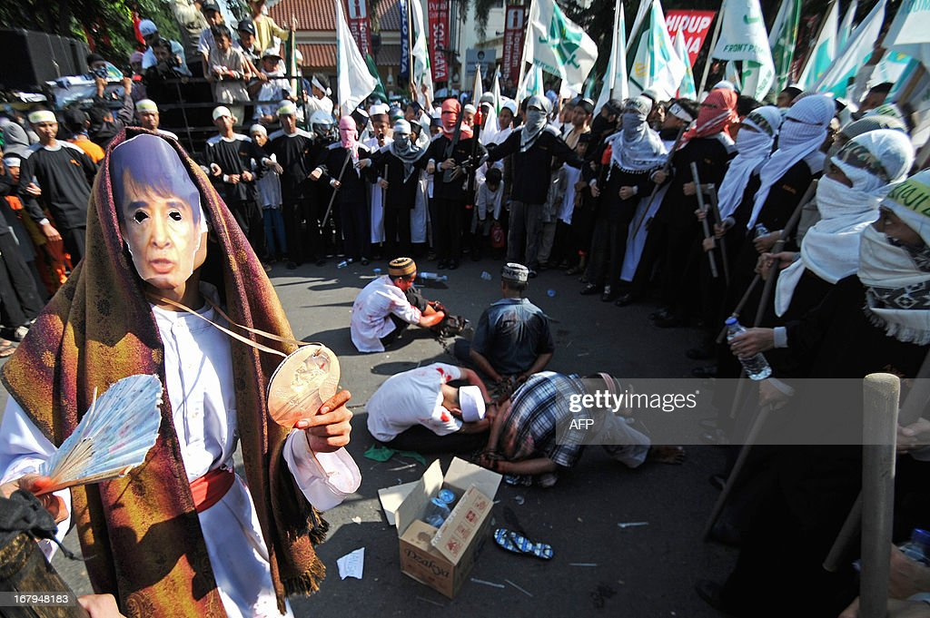 A protester from a hardline Muslim group wearing a mask showing a portrait of Nobel Peace Prize winner Aung San Suu Kyi takes part in an anti-Myanmar protest in Solo, Central Java, on May 3, 2013. The protest highlighted the growing anger in Muslim-majority Indonesia over a string of religious clashes in largely-Buddhist Myanmar, that have left many minority Muslims dead and tens of thousands displaced. Meanwhile, two Indonesians were detained over a plot to bomb the Myanmar embassy in Jakarta, officials said. AFP PHOTO / ANWAR MUSTAFA