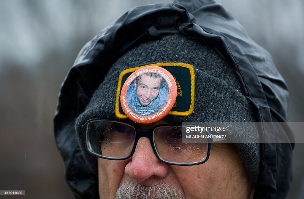 A protester from the Bradley Manning Support Group stands under the rain during a rally at the entrance of Fort George G. Meade military base in Fort Meade, Maryland on November 27, 2012. Manning is accused of downloading 260,000 US diplomatic cables, videos of US air strikes and US military reports from Afghanistan and Iraq between November 2009 and May 2010 and turning them over to WikiLeaks in what has been called one of the most serious intelligence breaches in US history.