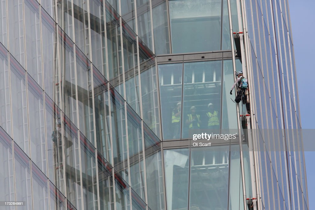 A protester from the environmental charity Greenpeace is watched by workers as she attempts to scale the tallest building in western Europe, The Shard, in a bid to unveil a giant banner from the top on July 11, 2013 in London, England. The six female protesters began their unauthorised ascent of the 310 metre high skyscraper shortly after 4am with the intention of highlighting the environmental damage caused by drilling for oil in the Arctic by Shell.