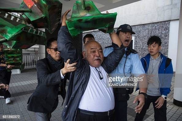 A protester from the League of Social Democrats holds a model tank made of cardboard as police remove him from an area during a protest against the...