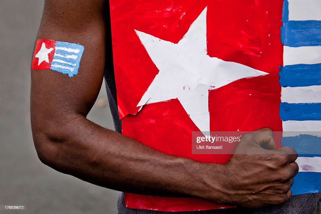 A protester from the Papuan Students Alliance holds the Morning Star flag during a protest against the signing of the New York Agreement In 1962 on August 15, 2013 in Yogyakarta, Indonesia. The demonstrations are a show of support for the opening of the Free West Papua Campaign office in the Netherlands which aims to help the current struggle for freedom in West Papau. The New York Agreement was a treaty signed between Netherlands, Indonesia and the UN which was intended to end a territorial dispute between Indonesia and West Papua.
