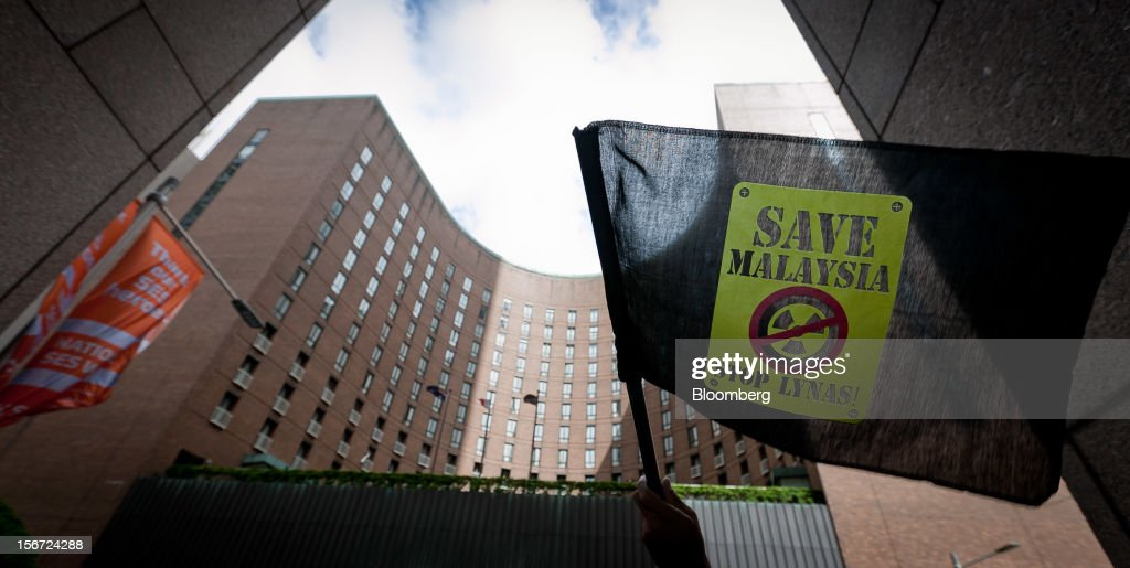 A protester from the Save Malaysia Stop Lynas group waves a flag during a demonstration outside the Sofitel Sydney Wentworth hotel, the venue for Lynas Corp.'s annual general meeting, in Sydney, Australia, on Tuesday, Nov. 20, 2012. The Save Malaysia Stop Lynas group will appeal a decision by the Kuantan High Court in the Malaysian state of Pahang, where Lynas's rare-earth refinery is located, that rejected an application for an injunction against the company's temporary operating license. Photographer: Ian Waldie/Bloomberg via Getty Images