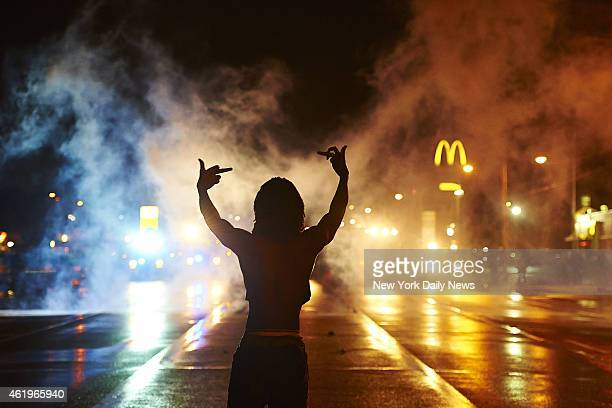 Protester gestures angrily at cops as tear gas fills the streets of Ferguson after curfew early Sunday One person was gravely injured in shooting...