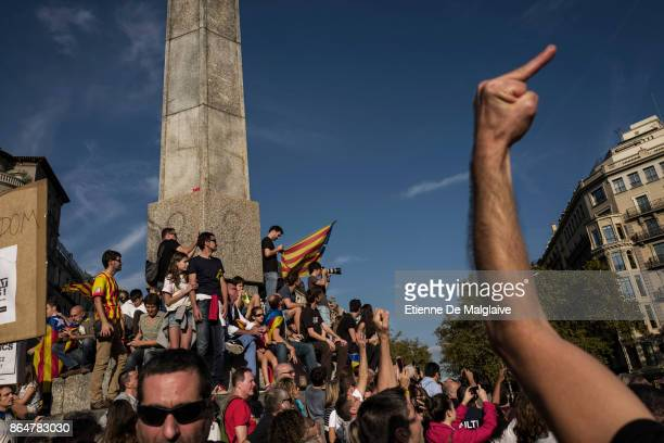 Protester gestures at a hovering police helicopter as massive crowd rally to demand the release of imprisoned Catalan leaders Jordi Sanchez and Jordi...