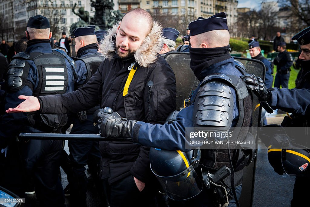 A protester gestures next to a riot police officer on the Place de la Nation in Paris on February 9, 2016, during a demonstration by non-licensed private hire cab drivers, known in France as VTC (voitures de tourisme avec chauffeur or tourism vehicles with chauffeur). VTC drivers continued a fifth day of protests on February 9 against measures granted by the French prime minister to taxi drivers. / AFP / Geoffroy Van der Hasselt
