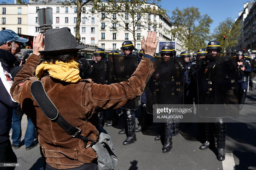 A protester gestures towards French anti riot police during a clash during the traditional May Day demonstration in Paris on May 1, 2016.