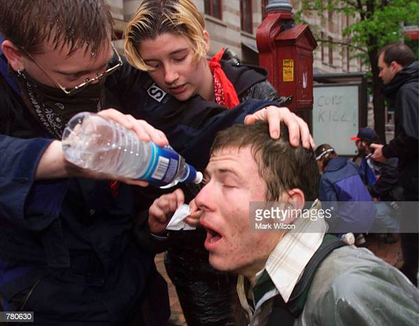 A protester gets his eyes washed out with water after getting hit with pepper spray April 17 2000 in Washington DC Hundreds of people participated in...