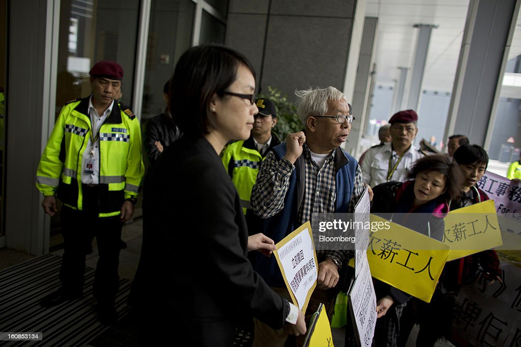 """A protester hands a petition letter to a government representative at the Central Government Complex during a march organized by labor unions in Hong Kong, China, on Thursday, Feb. 7, 2013. The Financial Services and the Treasury Bureau and the city's Companies Registry put forward a proposal to """"enhance protection of the privacy of personal information,"""" in November as part of a consultation paper on a new companies ordinance. The proposed amendments would make tracing the personal details of company directors in the city more difficult. Photographer: Lam Yik Fei/Bloomberg via Getty Images"""