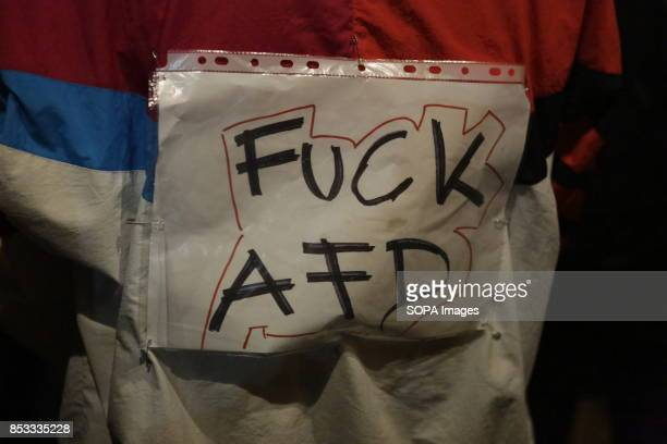 A protester has a sign on his jacket that reads 'Fuck AfD' Hundreds of protesters gathered outside a club near the central Alexanderplatz in Berlin...
