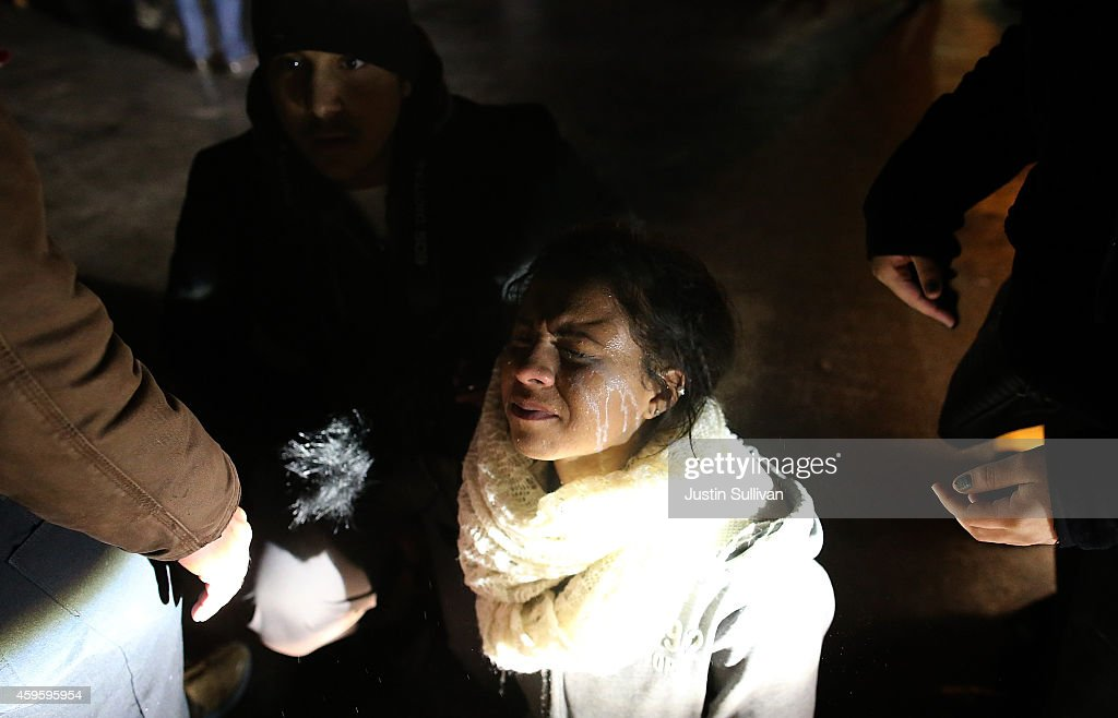 A protester has her eyes flushed after being sprayed with pepper spray by police who were dispersing a crowd from in front of the Ferguson police...