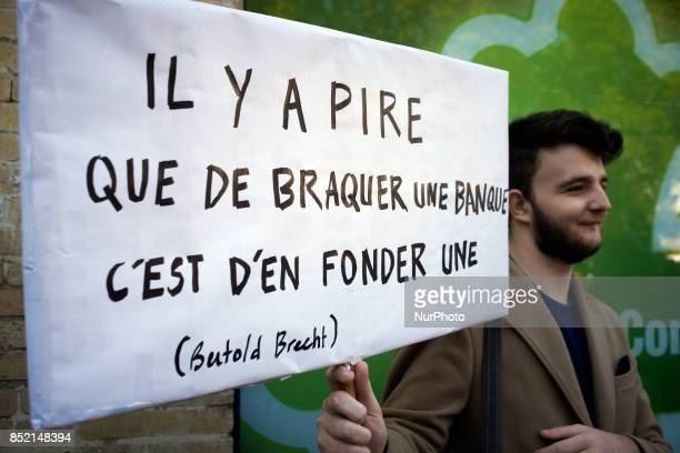 A protester hels a placard reading 'It's worse to open a bank than to rob one' a citation of Bertold Brecht' during a demonstration in Toulouse...