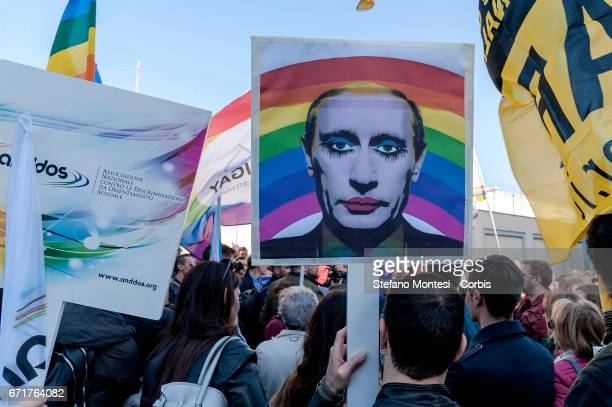 Protester hold a 'gay clown' poster of Russian President Vladimir Putin during the demonstration of LGBT Associations in front of the Russian Embassy...