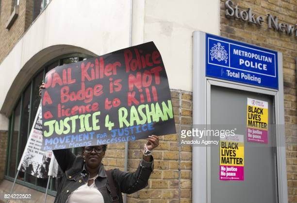 A protester hold a placard in a vigil for Rashan Charles outside Stoke Newington Police Station in London England on July 29 a week after the...