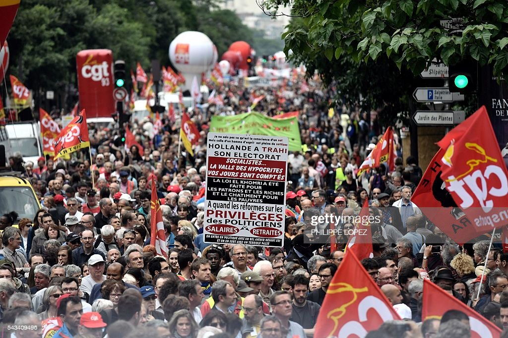 Protester hold placards and wave flag as they march during a demonstration against controversial labour reforms, on June 28, 2016 in Paris. Thousands of people took to the streets of Paris today in the latest protest march in a marathon campaign against the French Socialist government's job market reforms. / AFP / PHILIPPE