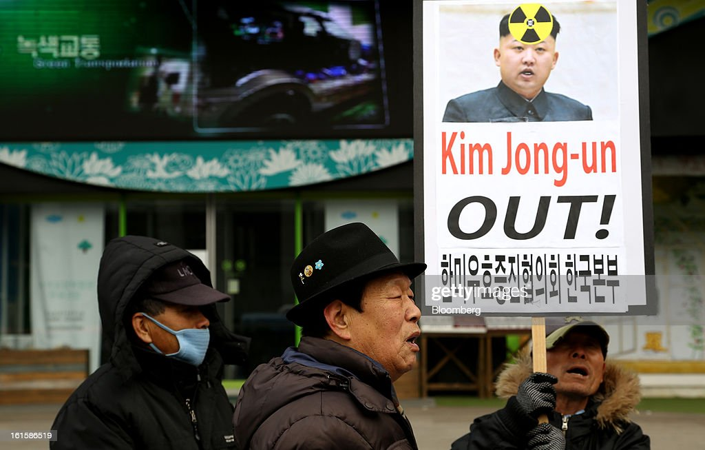 A protester holding a banner which says, 'Kim Jong Un Out!' in English and two other men participate in a demonstration against North Korea's nuclear test in Seoul, South Korea, on Tuesday, Feb. 12, 2013. North Korea conducted its third underground nuclear test today, underscoring a disregard for an international community that has already isolated the totalitarian state from the global economy. Photographer: SeongJoon Cho/Bloomberg via Getty Images