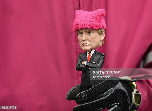 A protester holding a Donald Trump doll wearing a pink cap marches in Washington DC during the Womens March on January 21 2017 Hundreds of thousands...