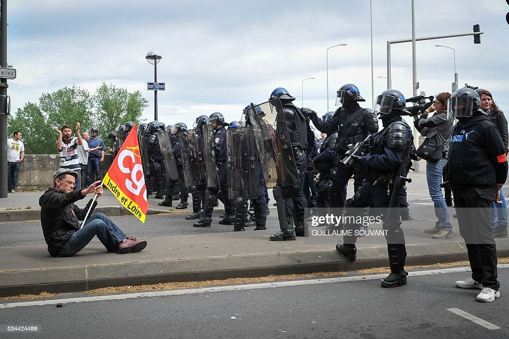 A protester faces riot police during a demonstration against the government's planned labour law reforms on May 26, 2016 in Tours, Central France. The French government's labour market proposals, which are designed to make it easier for companies to hire and fire, have sparked a series of nationwide protests and strikes over the past three months. The sign reads 'Our rights are on holidays in Panama'. / AFP / GUILLAUME