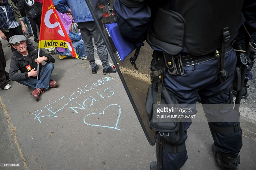 A protester holding a French CGT union's flag faces riot police during a demonstration against the government's planned labour law reforms on May 26, 2016 in Tours, Central France. The French government's labour market proposals, which are designed to make it easier for companies to hire and fire, have sparked a series of nationwide protests and strikes over the past three months. The writing reads 'join us'. / AFP / GUILLAUME