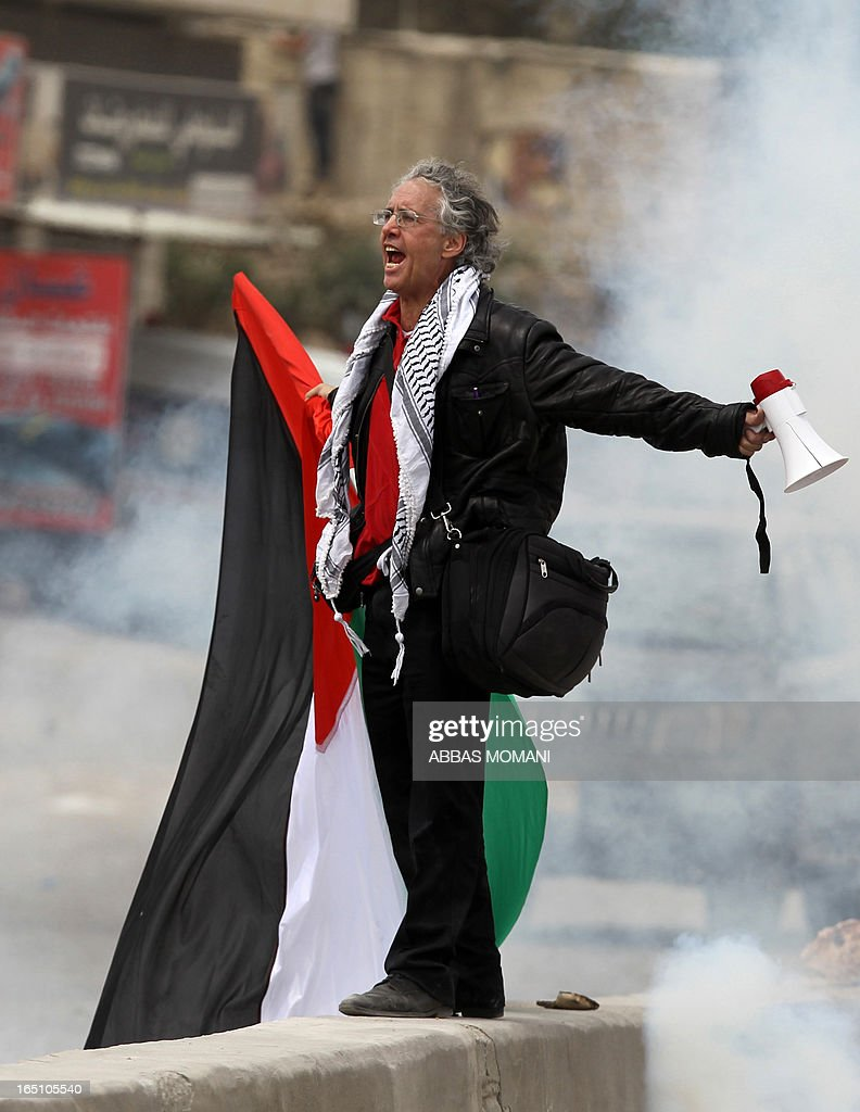 A protester holding a Palestinian flag shouts slogans during clashes between Palestinian protesters and Israeli soldiers following a rally commemorating the 37th anniversary of 'Land Day', on March 30, 2013 near the Qalandia checkpoint in the Israeli occupied West Bank. Nearly 200 Palestinians clashed with Israeli forces in Qalandia, who responded with tear gas.