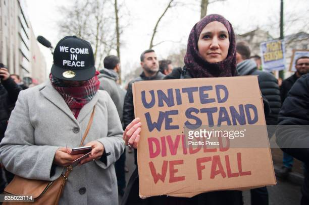 A protester holding a placard with the words 'United we stand Divided we fall' on it stands next to a protester with a banner at the protest against...