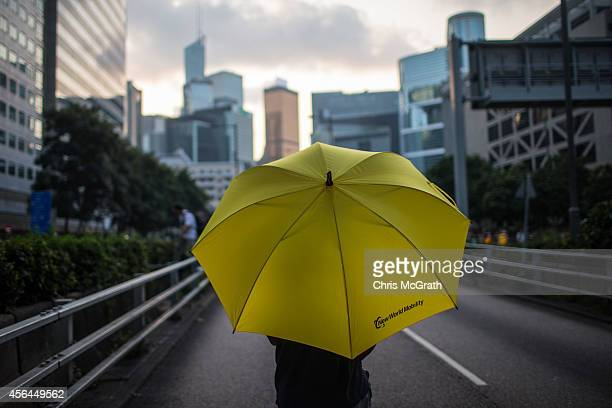 A protester holding an umbrella stands on the street close to the Hong Kong Government Complexon October 1 2014 in Hong Kong Hong Kong Thousands of...