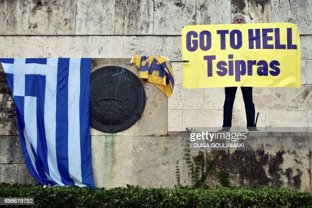A protester holds a banner as he gathers with others in front of the Greek Parliament in Athens on June 20 during a demonstration against the...