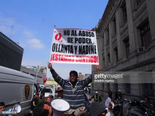 A protester holds a banner during a demonstration in support to former Peruvian President Ollanta Humala while a vehicle transports him and his wife...