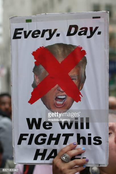 A protester holds a banner reading 'Everyday We Will Fight His Hate' with an crossed out image of Donald Trump during a rally against US President...